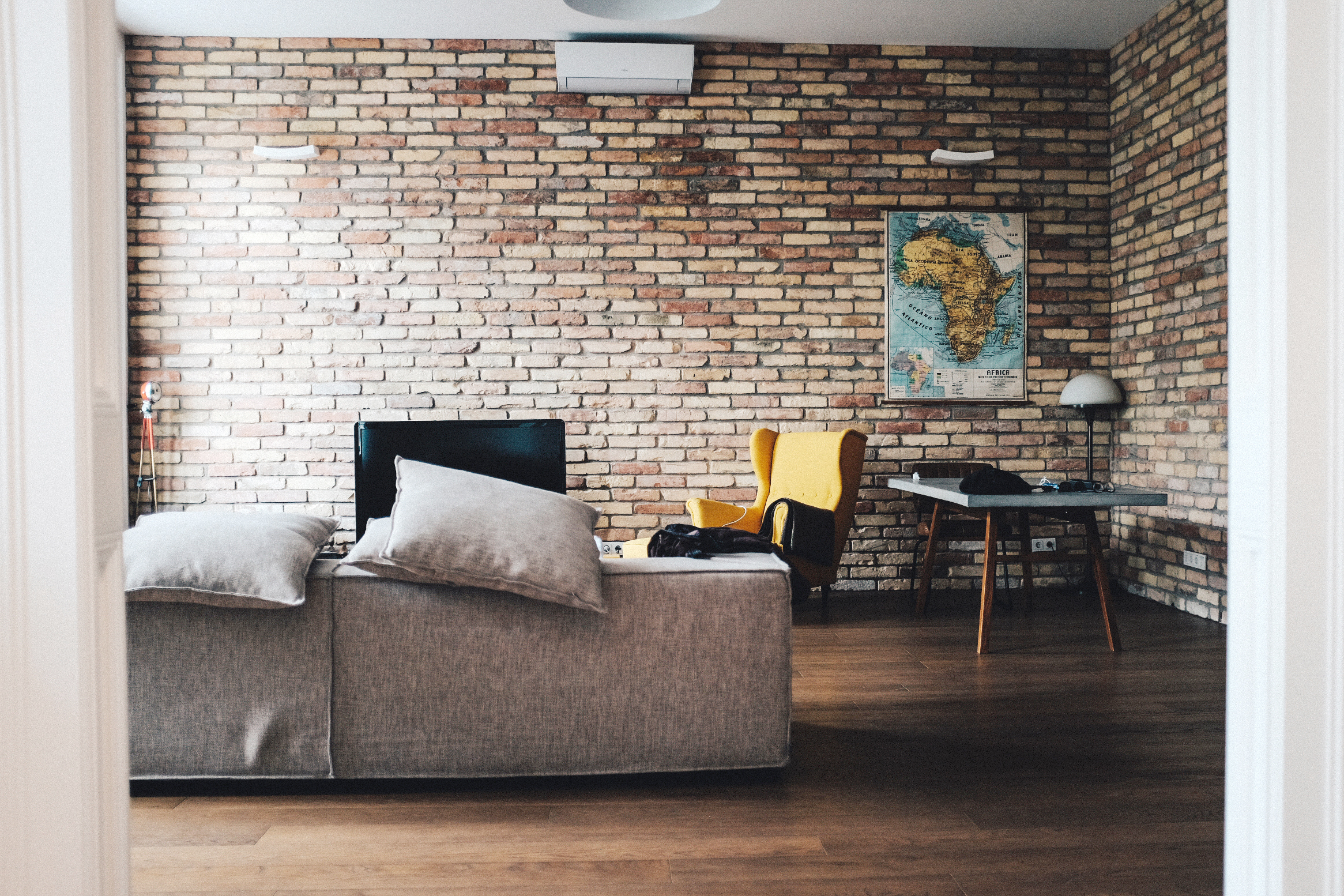 Wall to Wall Exposed Brick Living Room with Couch, Yellow Chair, Modern Table, Map of Africa on the Wall