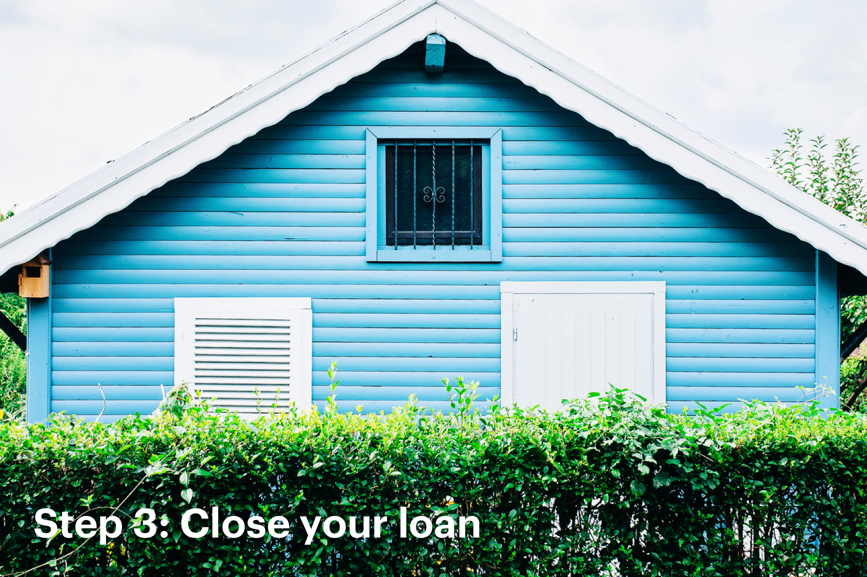 Close Up of Side Panel of Blue Home Behind Green Shrubs with Text that Reads: Step 3: Close Your Loan